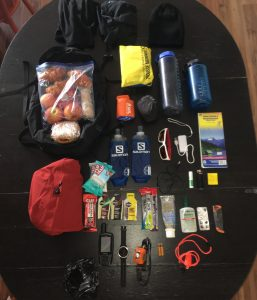 Water, snacks, maps, first aid kit and other items for a day hike laid out on a table