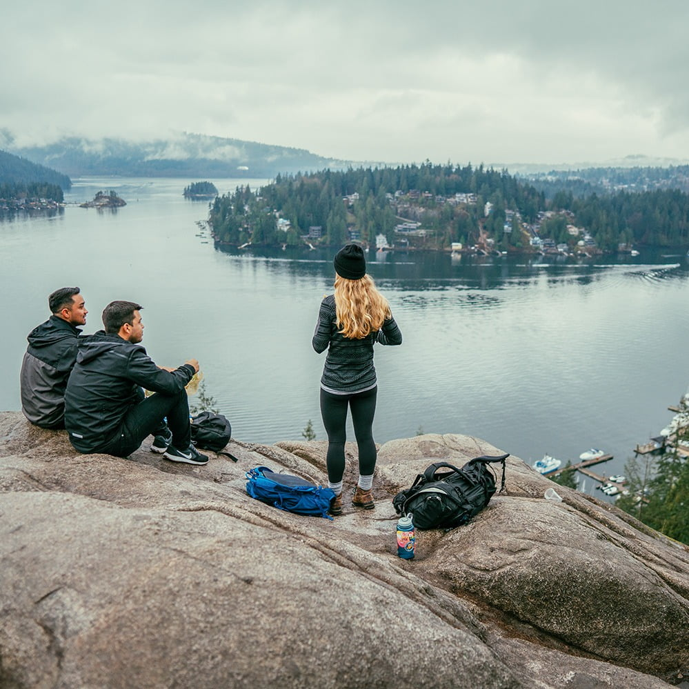 Three hikers on a rock overlooking a bay on an outdoor adventure