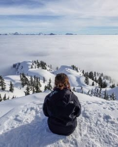 Female Sitting At The End Of A Beautiful Snowshoeing Trail Near Vancouver