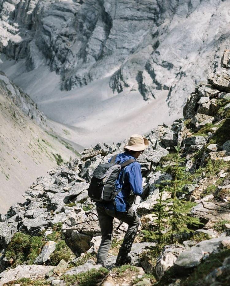 Man walking across rock debris field at the Cascade Amphitheatre. 5 Best Hikes: Banff, Alberta