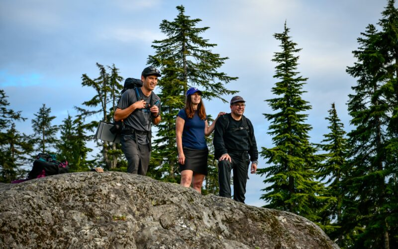 People smiling at top of a mountain