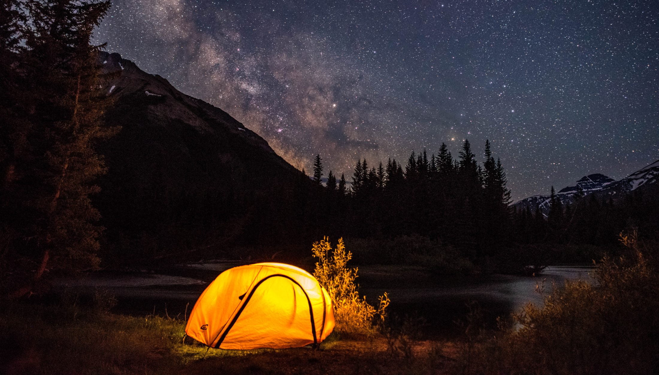 A Tent Glowing Under A Starry Night Sky, With A Mountain And Trees In The Background.
