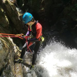 A Man At The Top Of A Waterfall Attached To Ropes While Canyoning In Vancouver