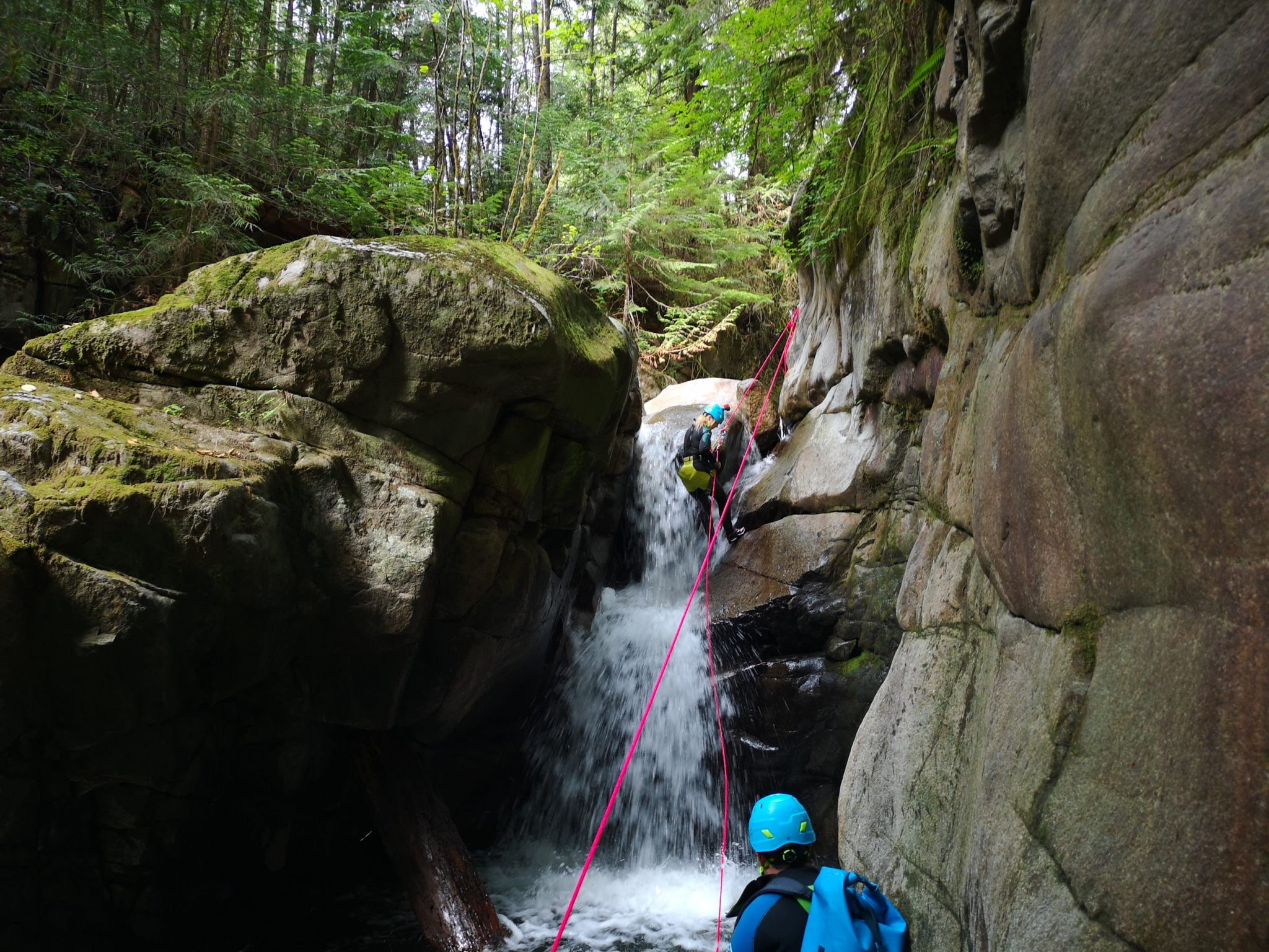 A girl rappels down a waterfall while canyoning in Vancouver