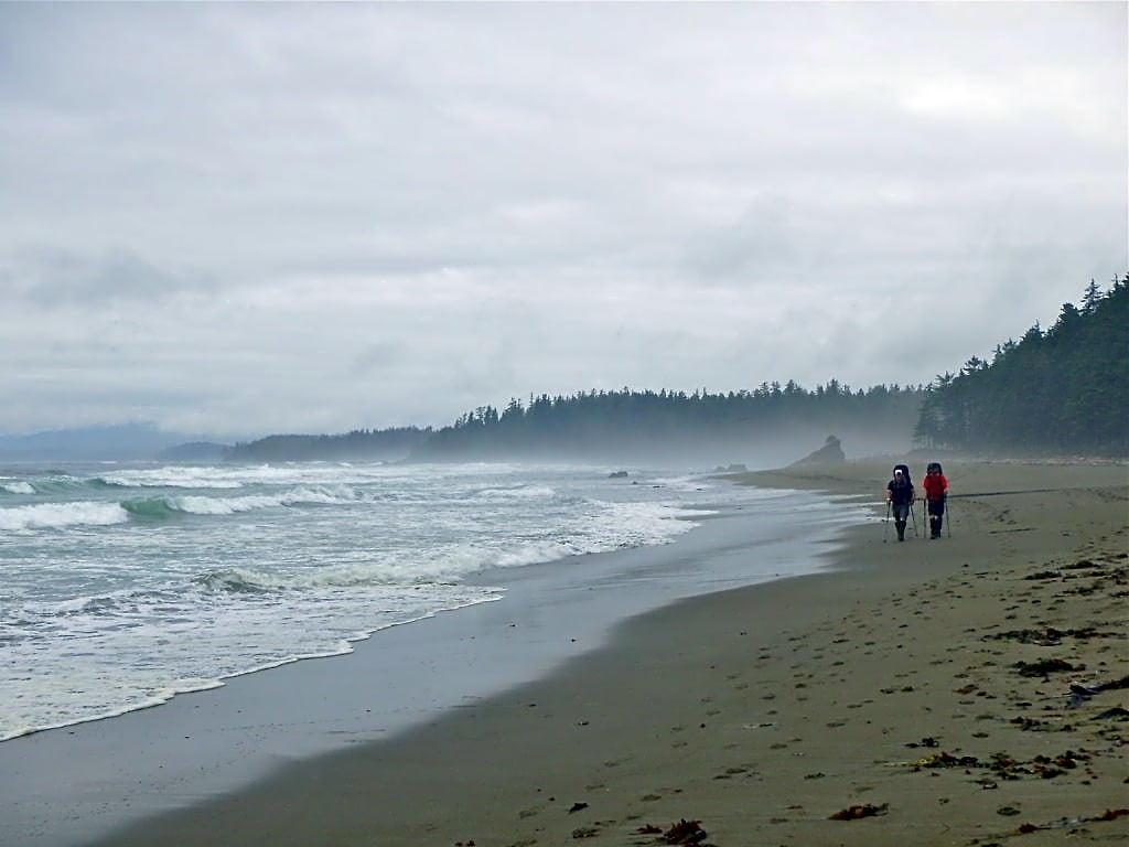 Two hikers on a beach on the West Coast Trail