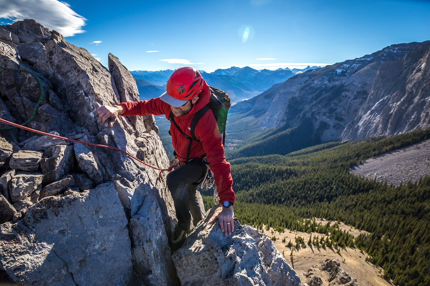 An ACMG Rock Climber High Above A Valley With Mountains In The Background