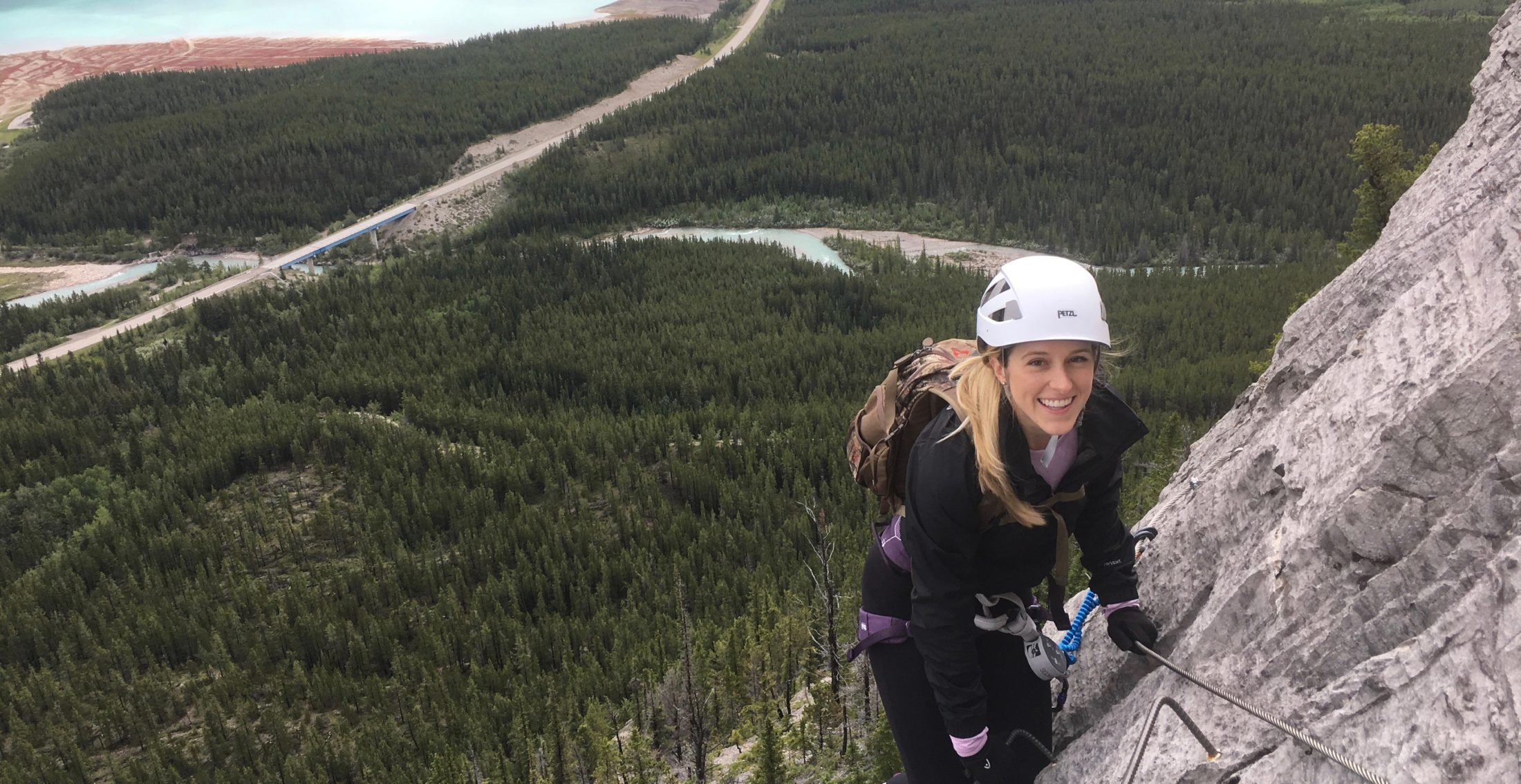 A girl wearing a helmet climbing a via ferrata with a forest and lake below