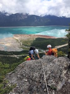 A Group Of Climbers At The Top Of Mt Stelfox With A Blue Lake Below