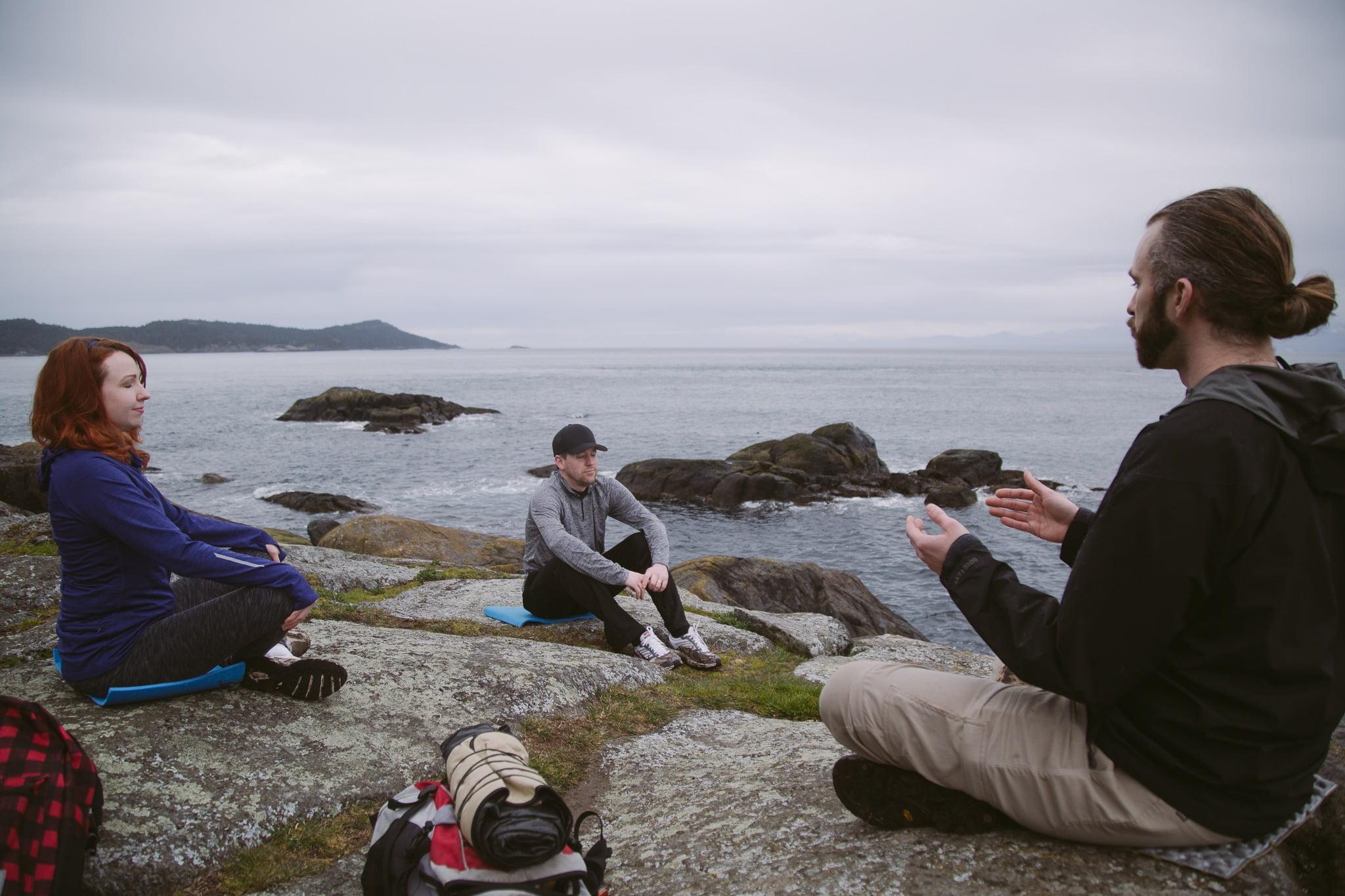 Three People Sat On Rocks Beside The Sea Practicing Wellness And Meditation