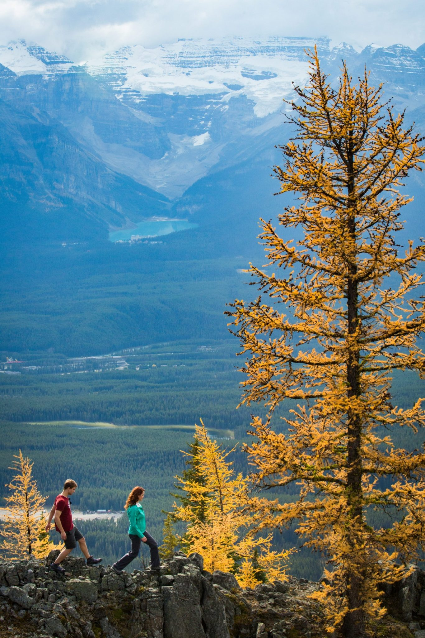 Couple hiking past autumn trees with views down the valley to Lake Louise in Banff National Park, Alberta