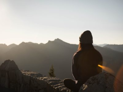 Girl Sat On A Rock At Sunrise, Overlooking Mountains Practicing Meditation