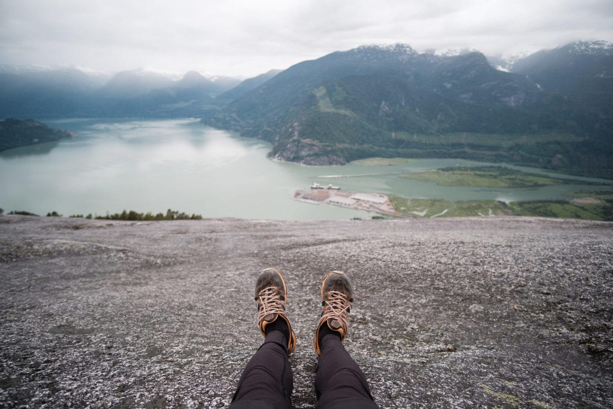 Person's Legs In Focus On Top Of Mountain