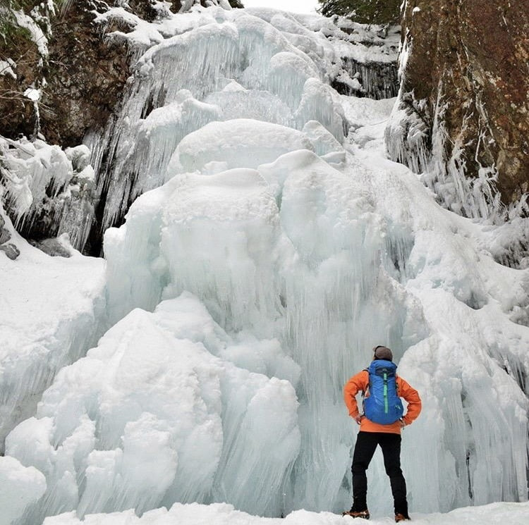 Man Staring At Frozen Waterfall In Canadian Winter