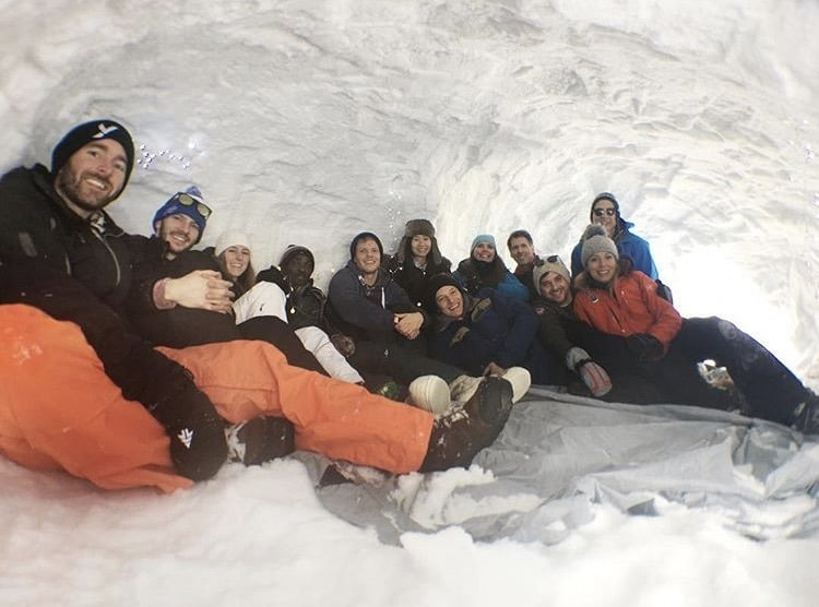 Group of people sitting warmly in a Quinzhee