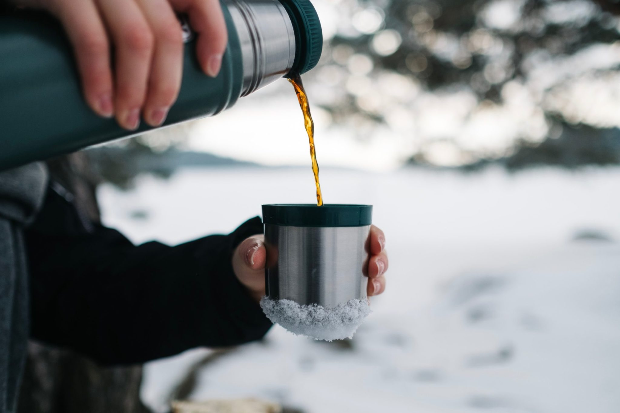 Person Pouring A Hot Beverage Out Of An Insulated Mug In Mountains Near Canmore: Winter
