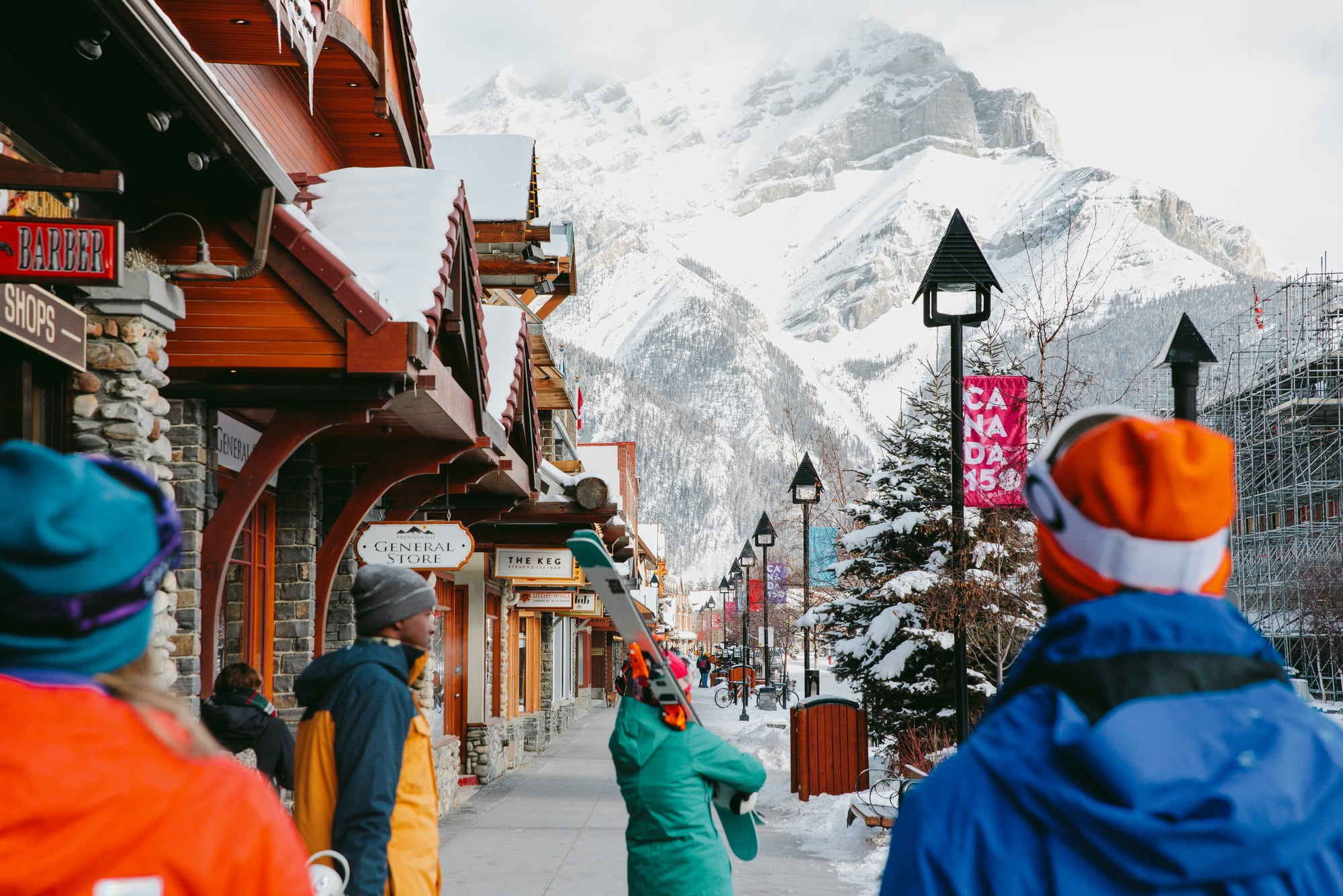People walking through town of Banff with skis