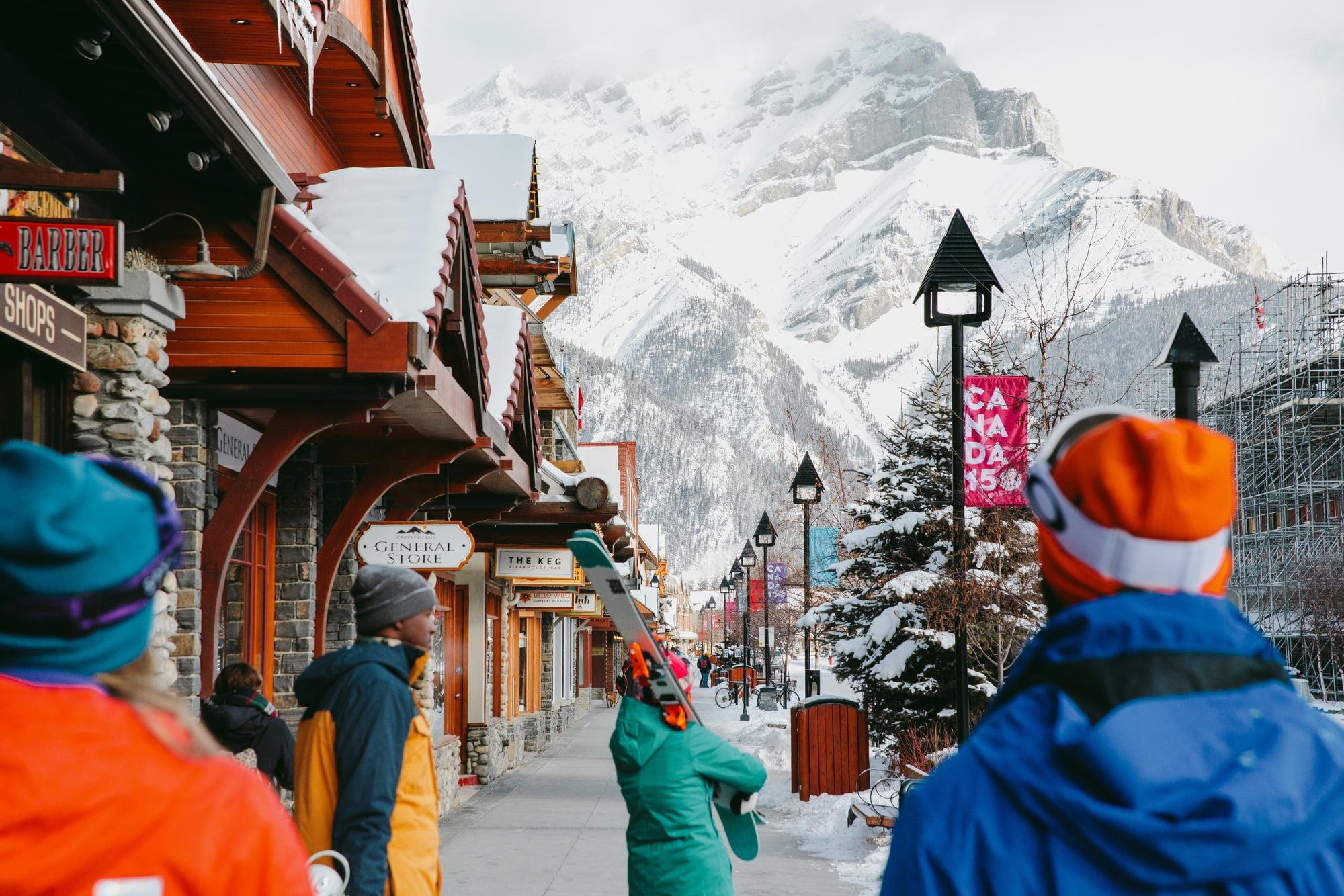 People walking through town of Banff with skis