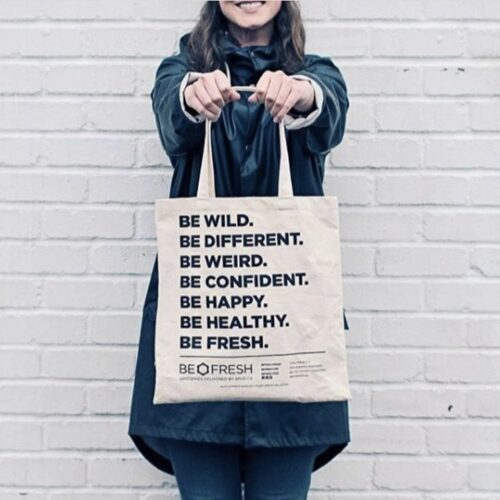 woman holding a reuseable bag, smiling