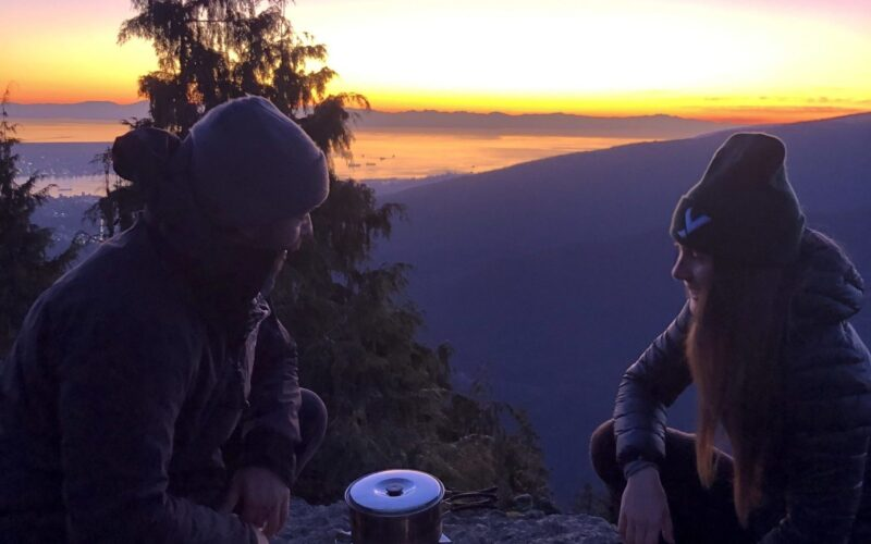 2 people backcountry cooking responsibly at sunset on a mountain