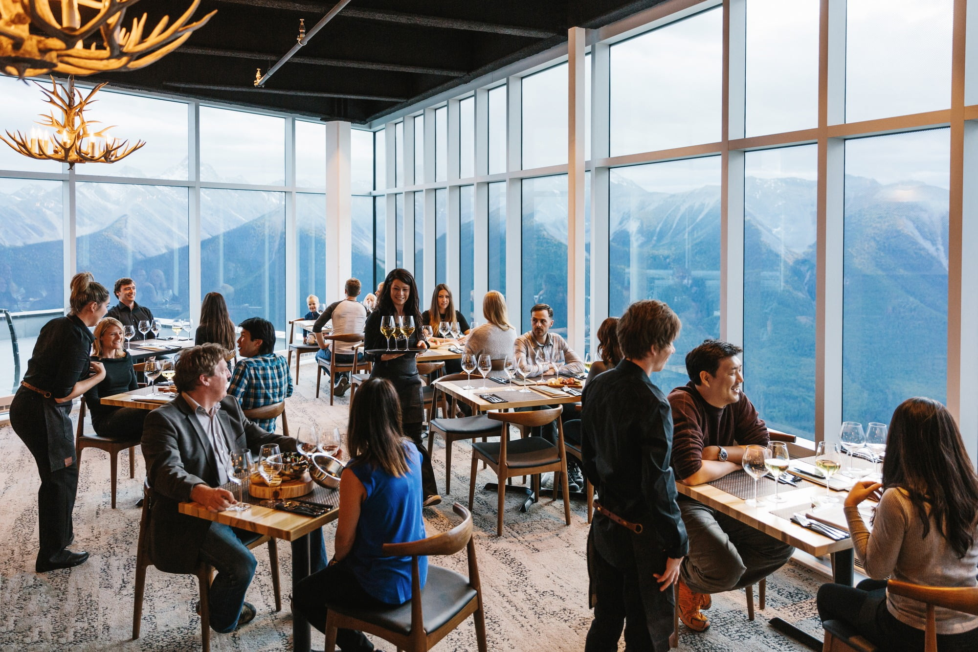 People Eating In Sky Bistro With Mountains Behind Them