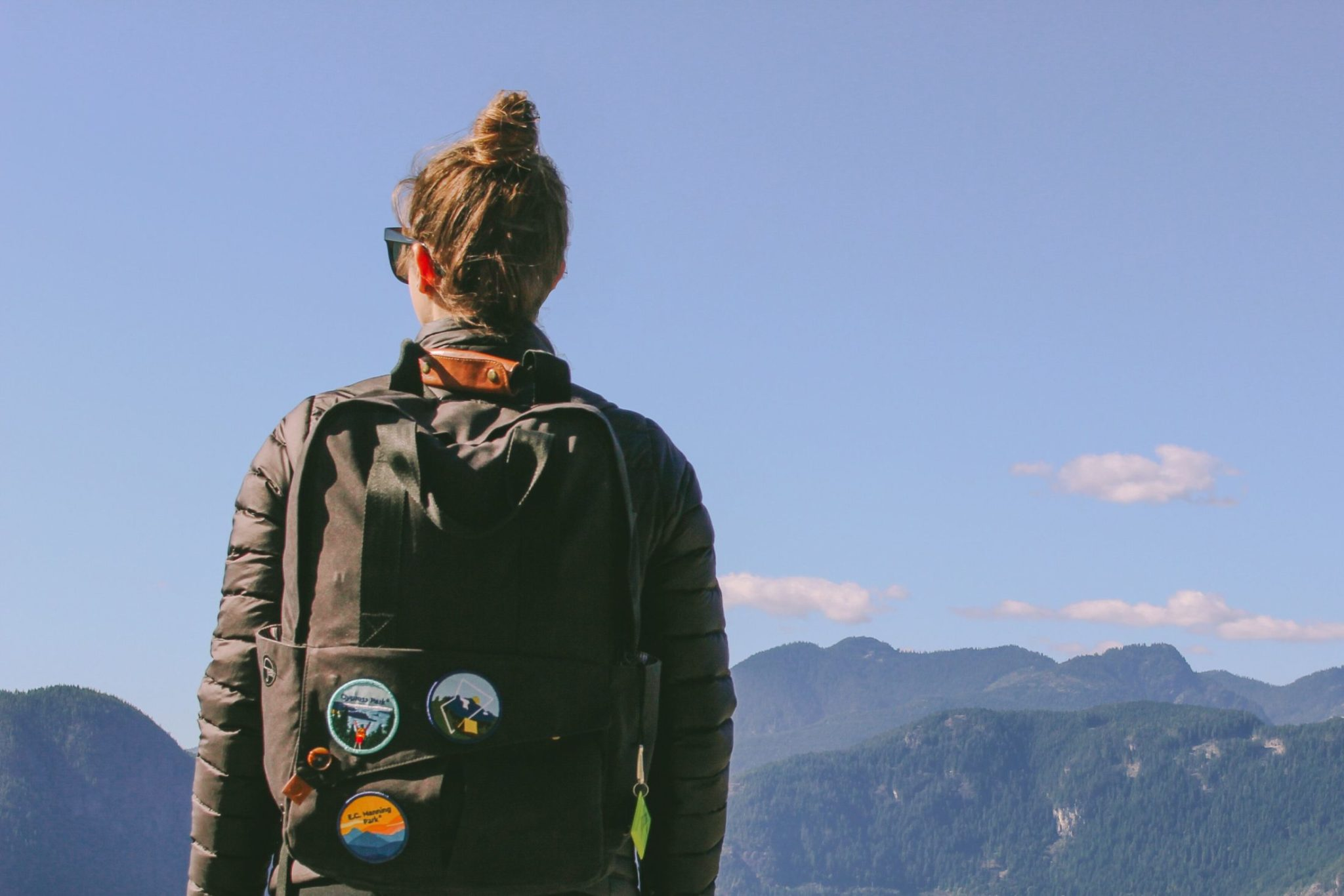 A girl with her back to the camera, wearing a backpack covered in BC Parks Foundation patches