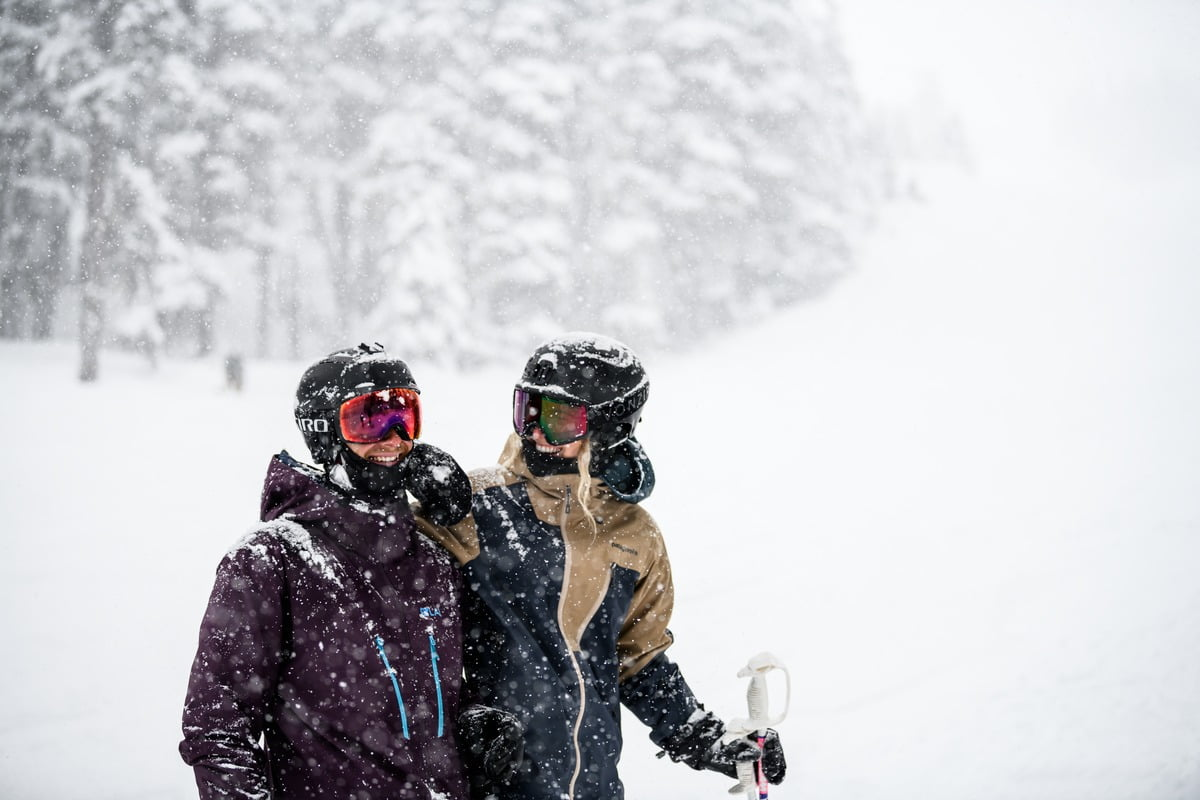 A couple in snowfall at Whistler, BC