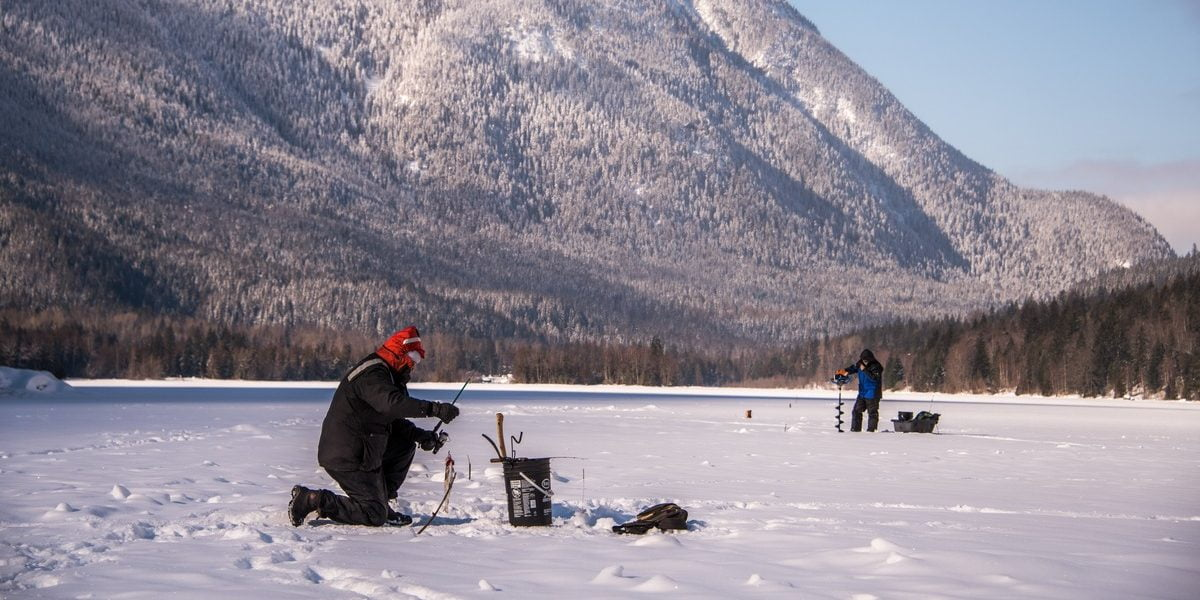 A person ice fishing on a frozen lake, with a snowy mountain in the background