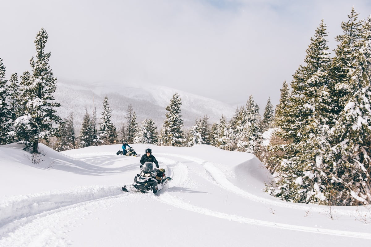A Snowy Landscape With Two Snowmobilers In The Backcountry