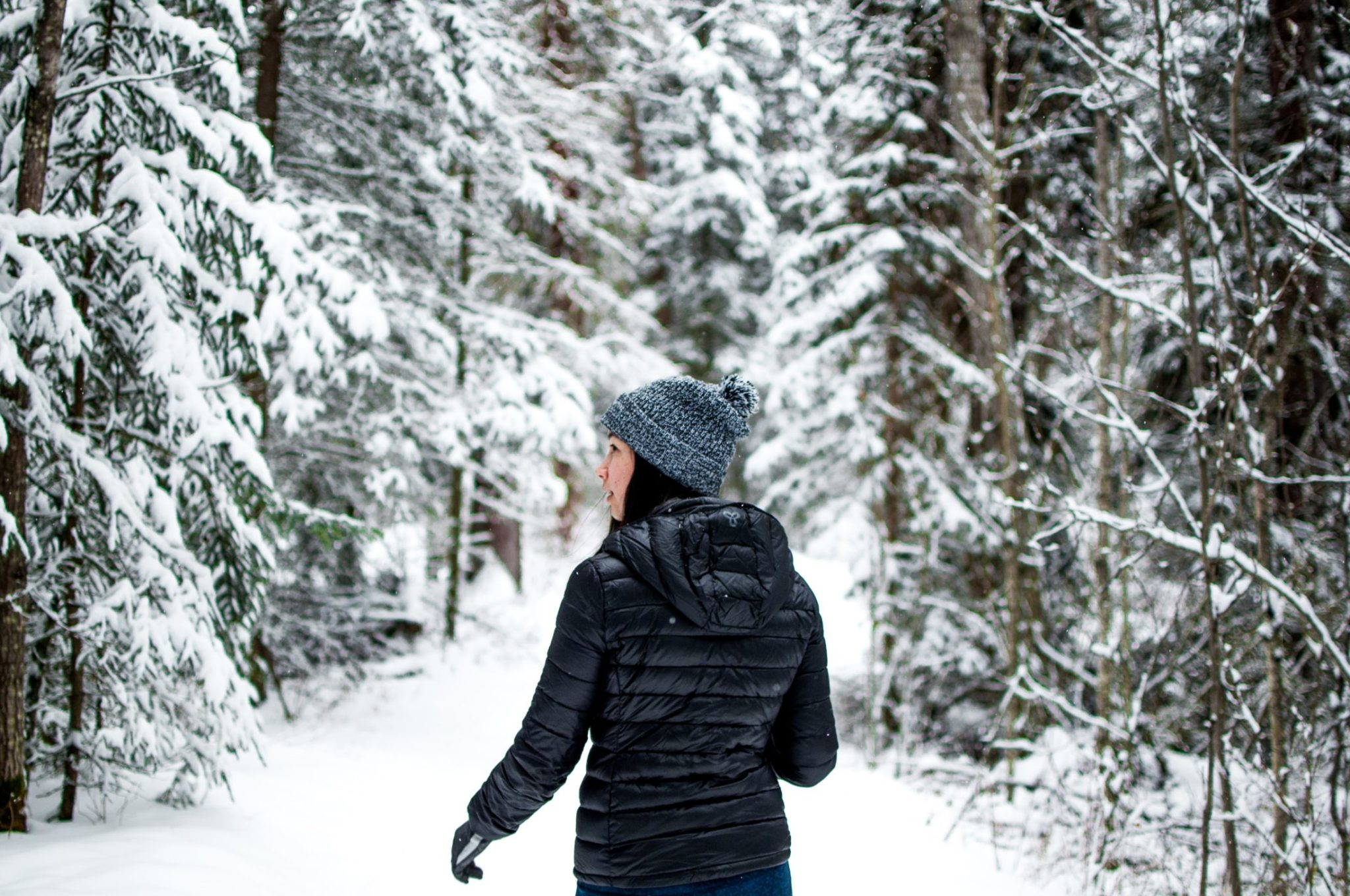 A Girl Walking Through A Snowy Forest In Winter