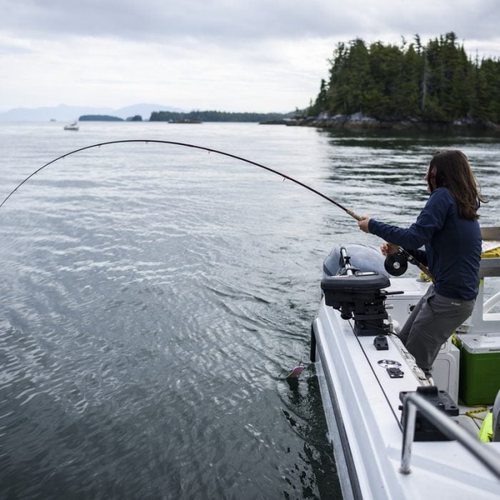 Woman Fishing On The Ocean Off A Boat In British Columbia