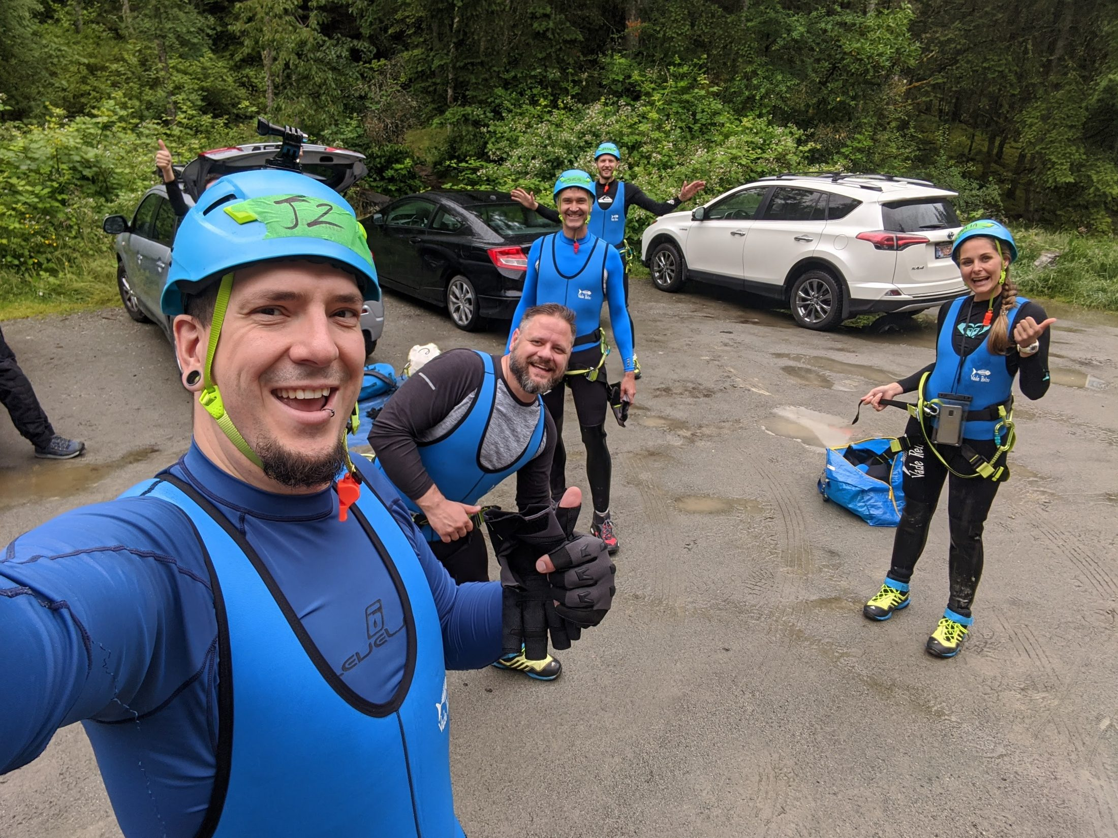 A Group Of People Dressed In Canyoning Gear Give A Thumbs Up In A Car Park Before Starting An Adventure