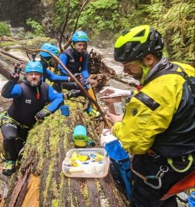 A Group Of People Wearing Canyoning Gear Eat Lunch Around A Log