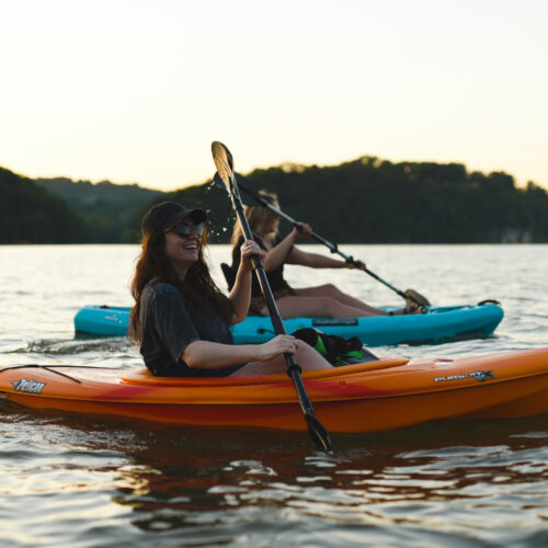 Two girls paddling in kayaks at sunset