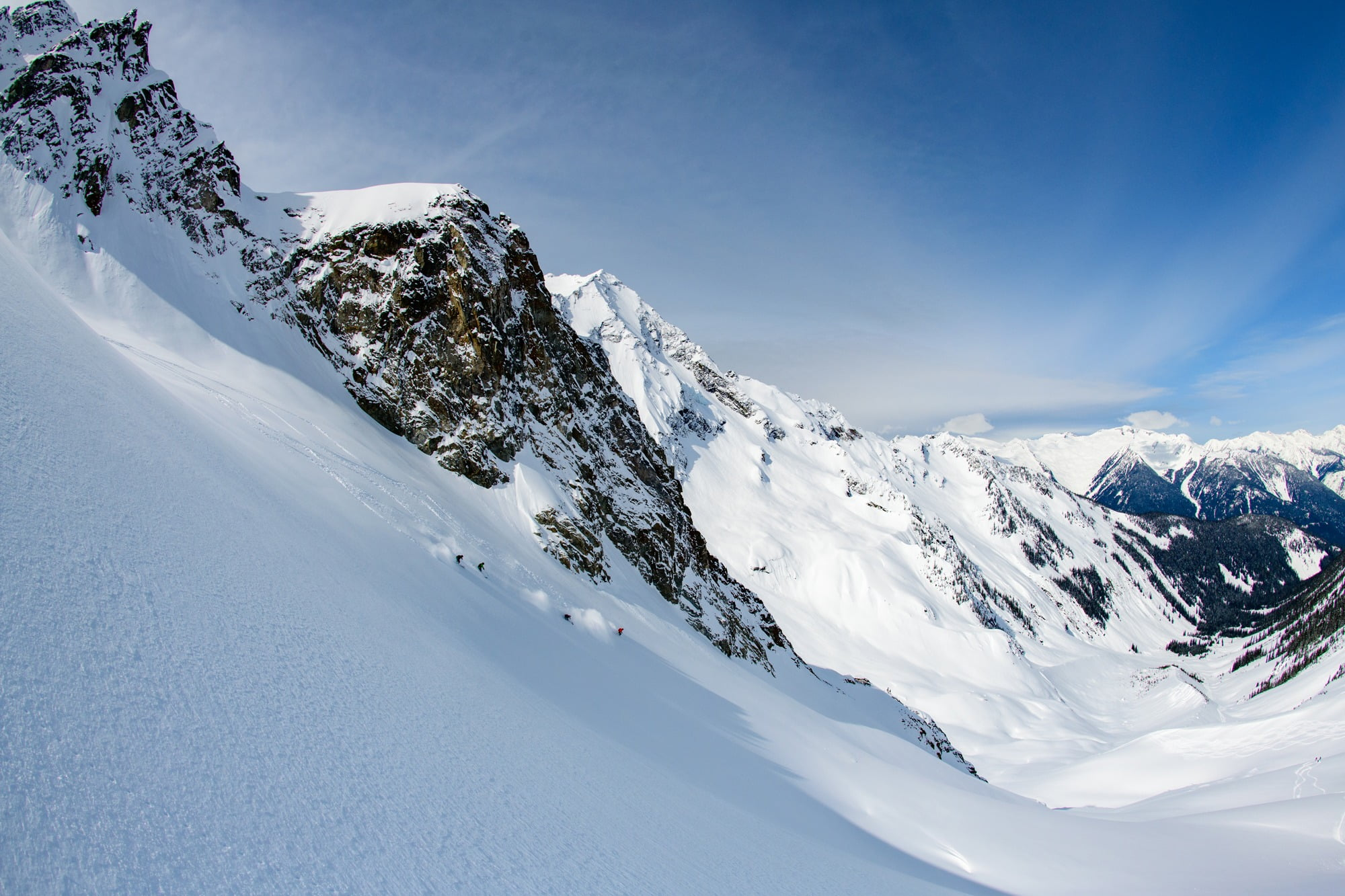 A Groups Of 4 People Heli-skiing In Revelstoke, BC. Huge Mountains In The Backdrop.