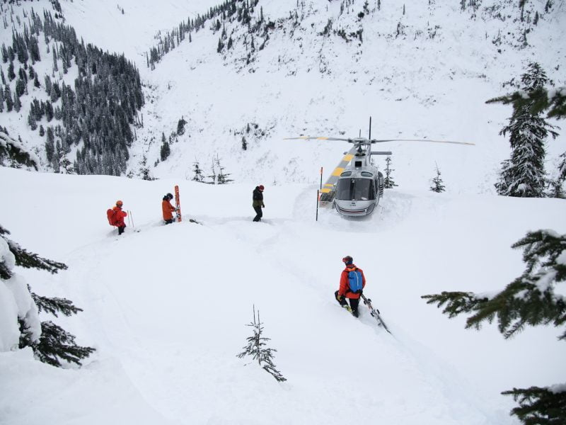 A Group Of People Heli-skiing Approach Their Helicopter In Deep Snow.