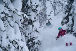 Two People Skiing Through Alpine Terrain In Deep Snow